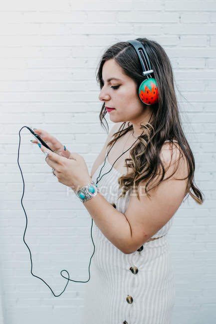 Side view of long haired attractive youngster woman checking play list in smartphone on white background — Stock Photo