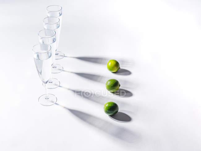 Kontrastierende Schatten aus Wassergläsern und grünen reifen Limetten auf weißem Hintergrund — Stockfoto