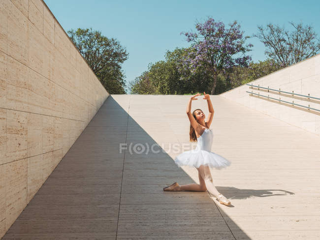 Ballerina performing with raising hands and stretching legs outside in bright sunny day — Stock Photo