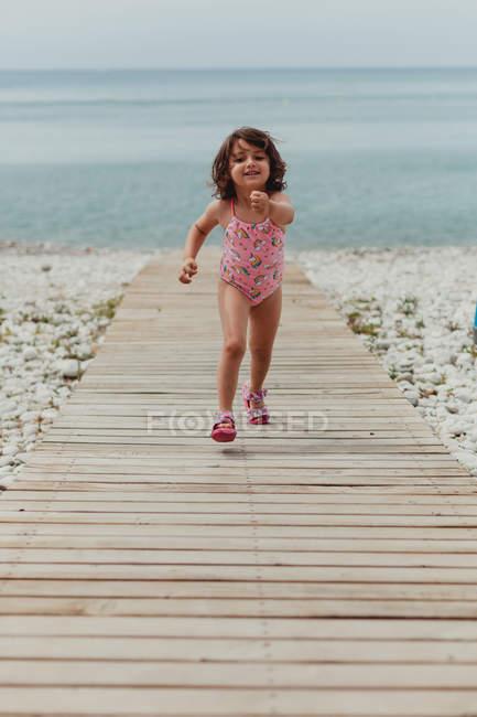 Счастливый ребенок в розовом купальнике, бегущий вдоль деревянного причала по морю — стоковое фото