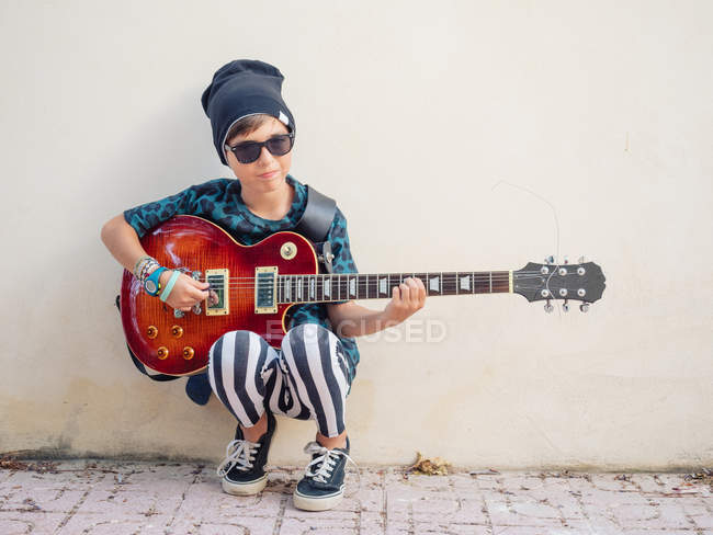 Cheeky active excited boy in colorful clothes playing guitar, leaning on background of white wall — Stock Photo