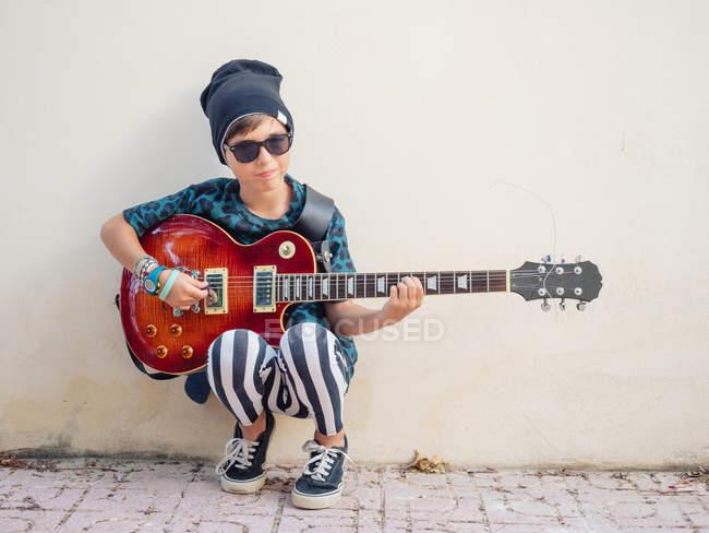 Frech aktiver aufgeregter Junge in bunten Klamotten, der Gitarre spielt, angelehnt an den Hintergrund einer weißen Wand — Stockfoto