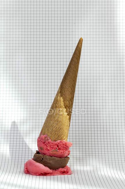Cône de crème glacée aux fraises et au chocolat tombé sur papier quadrillé — Photo de stock
