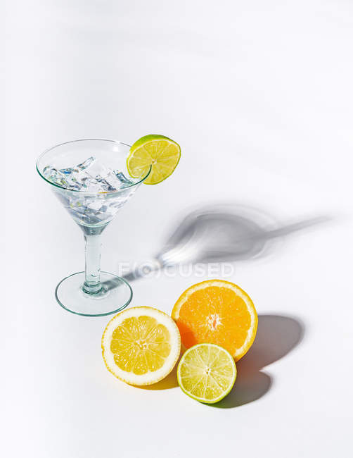 Glass of drink full of ice cubes and sliced orange, lime and lemon on white background — Stock Photo