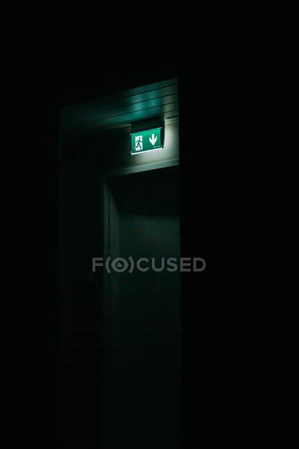 Зеленый знак выхода, сияющий над закрытой дверью в темной комнате — стоковое фото