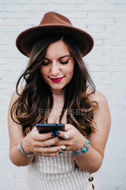 Donna attraente dai capelli lunghi in cappello messaggistica nel telefono cellulare — Foto stock