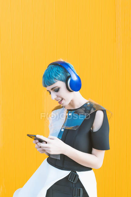 Cheerful informal woman in headphones browsing smartphone and listening to music while standing against vivid yellow wall — Stock Photo