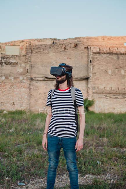 Amazed young bearded male exploring world wearing virtual reality glasses — Stock Photo
