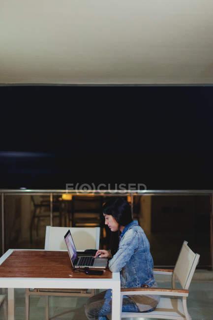 Бічний вид на молоду бреннетку в джинсах сидить за дерев'яним столом і працює на ноутбуці вдома. — стокове фото