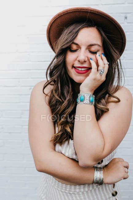 Молода приваблива жінка в капелюсі закриває очі і торкається обличчя, стоячи навпроти білого фону. — стокове фото