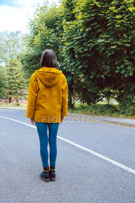 Vista posteriore della donna in cappotto giallo che cammina lungo la strada asfaltata sulla verde strada suburbana — Foto stock