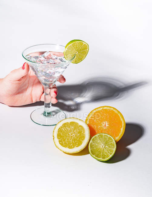 Female hand holding glass of drink full of ice cubes and sliced orange, lime and lemon on white background — Stock Photo