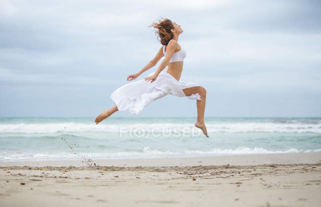 Attractive female in white outfit dancing on sand near waving sea — Stock Photo