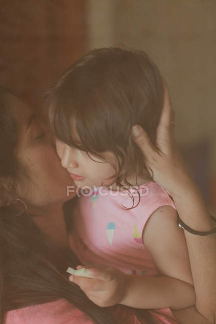 Vista dalla finestra della giovane madre bruna che bacia teneramente sua figlia a casa — Foto stock