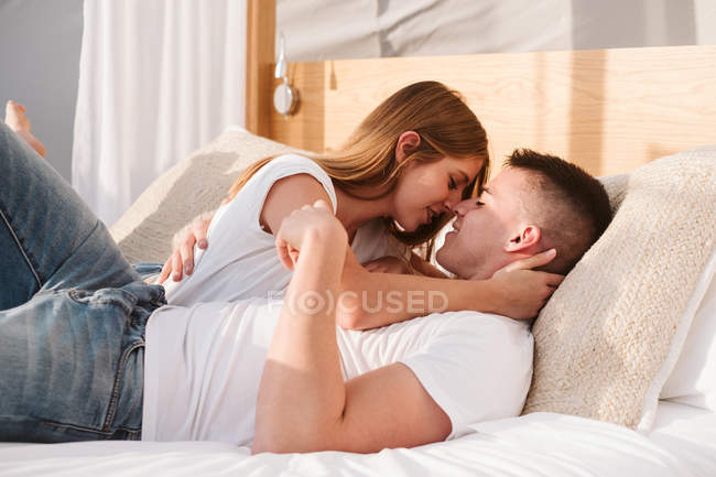 Young Romantic Couple In White T Shirts And Jeans Lying And Hugging In Bedroom Of Glamping Kissing Sensual Stock Photo 293866074
