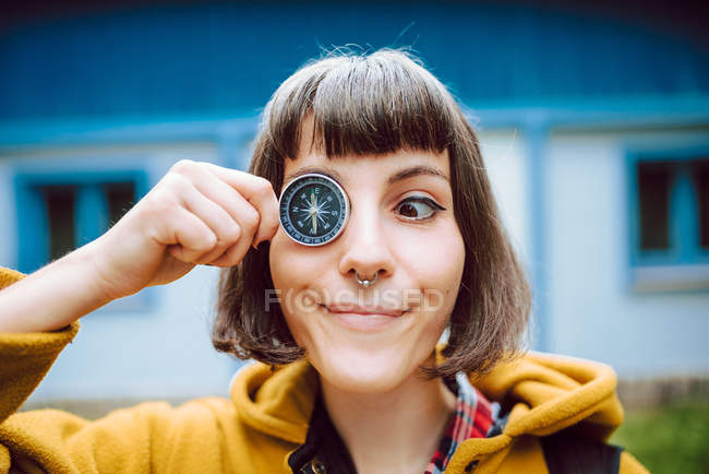 Cheerful young woman crossing eyes and holding retro compass near face while standing on blurred background of countryside house — Stock Photo