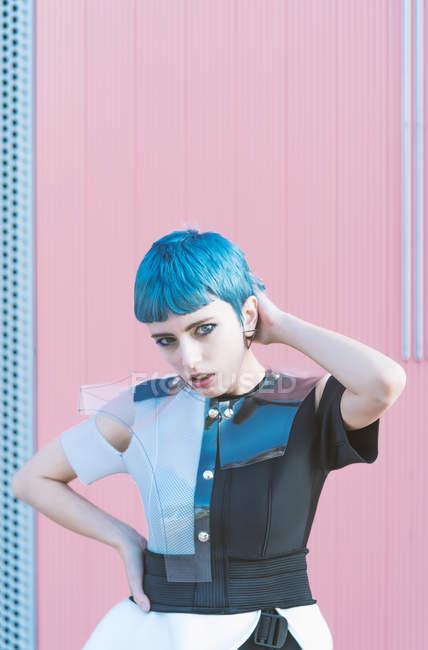 Mujer joven en vestido alternativo de moda tocando el pelo azul corto y mirando a la cámara mientras está de pie contra la pared rosa - foto de stock
