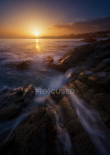 Picturesque view of clean sea water rolling and splashing near rough stones during wonderful sundown — Stock Photo