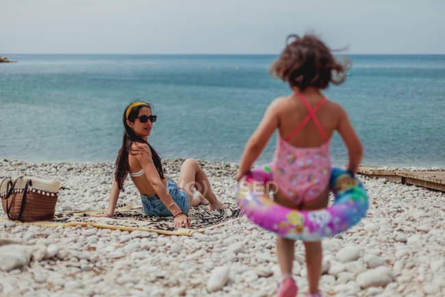 Vue de dos mère assise sur un rivage rocheux et regardant une petite fille à la mode en maillot de bain rose marchant sur une plage rocheuse — Photo de stock