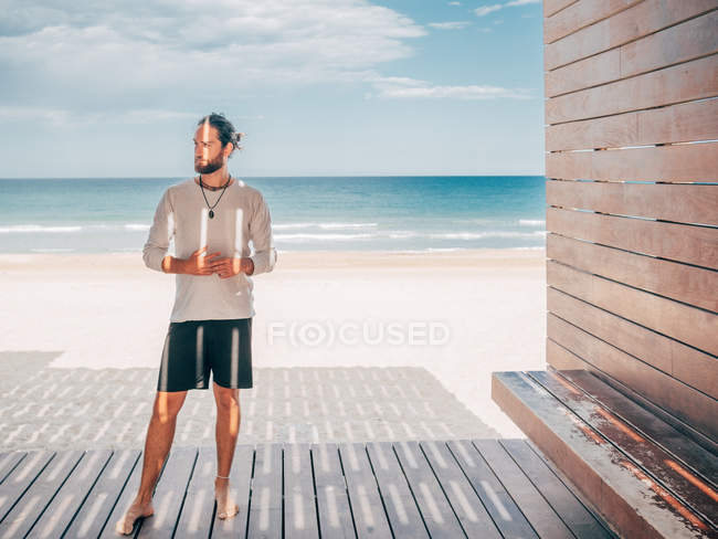 Homme barbu adulte debout reposant détendu sur une jetée en bois au bord de la mer regardant loin — Photo de stock