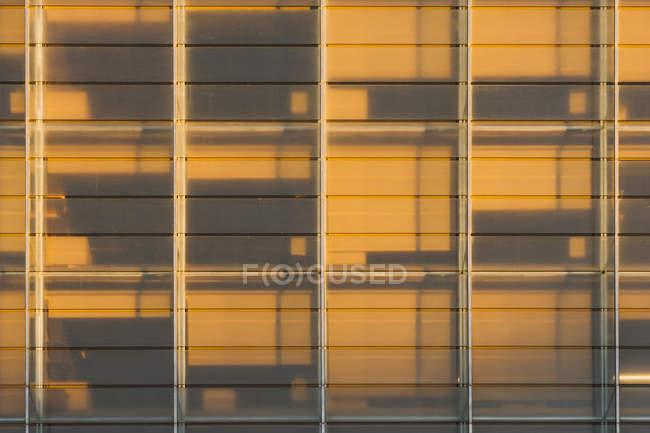 Rectangular windows of building with dark contrast shadow in sunset light — Stock Photo