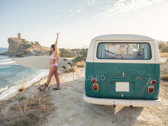 Encantadora mulher de cabelos longos vai surfar segurando prancha de surf perto de van vintage — Fotografia de Stock