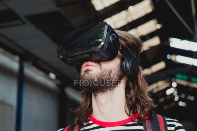 Interessierter junger Mann mit Virtual-Reality-Brille gestikuliert und erkundet verlassene Lagerhalle — Stockfoto