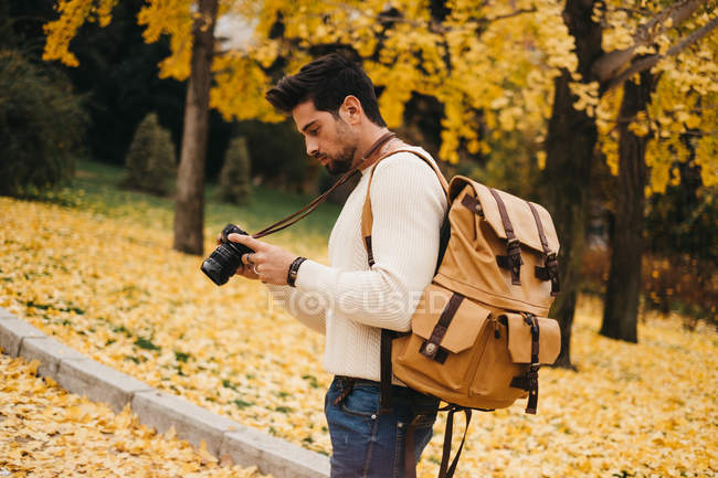 Bello giovane fotografo in piedi nel parco autunnale e tenendo la fotocamera — Foto stock