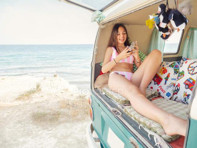 Стройная женщина в розовом купальнике улыбается и фотографирует лежащих на мягких подушках в багажнике трейлера на берегу моря в солнечный день — стоковое фото