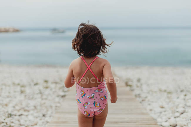 Back view of child in pink bathing suit running along wooden jetty by sea — Stock Photo