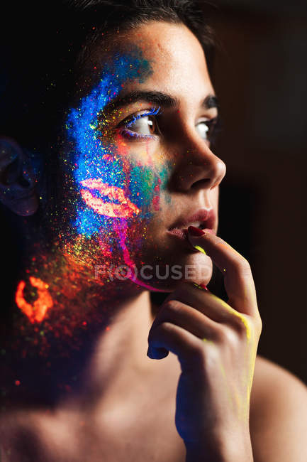 Side view of beautiful young woman covered with luminous paint on face touching lips with finger — Stock Photo