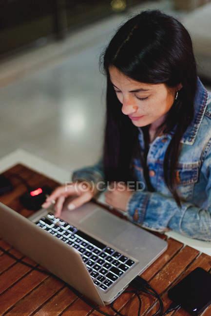 Visão superior da jovem morena de jaqueta jeans sentada à mesa de madeira e trabalhando no laptop em casa — Fotografia de Stock