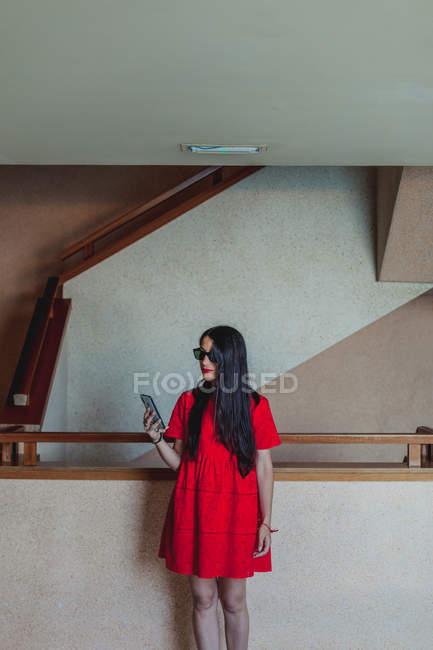 Серйозна мода молода брюнетка в червоній сукні і сонцезахисних окулярах стоять зі смартфоном в залі — стокове фото
