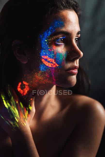 Retrato de una hermosa joven cubierta de pintura luminosa en la cara, cuello y mano mirando hacia otro lado - foto de stock