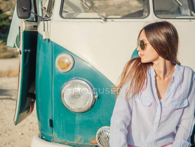 Sorrindo encantadora mulher com cabelos longos sentado no pára-choques e olhando ao longo — Fotografia de Stock