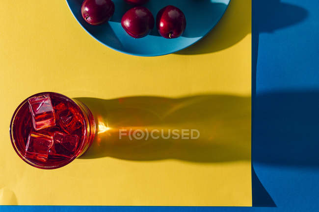 Красный напиток возле свежих фруктов — стоковое фото