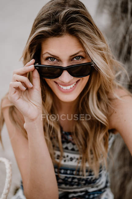 Close-up portrait of blonde woman in black sunglasses sitting on sand and looking at camera — Stock Photo