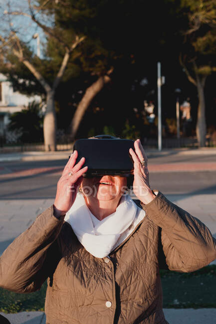 Бабуся, яка дивиться вперед, бачить новий змодельований світ. Старша жінка торкається неіснуючого об'єкта з піднятою рукою стоячи на розмитому тлі з міською вулицею — стокове фото