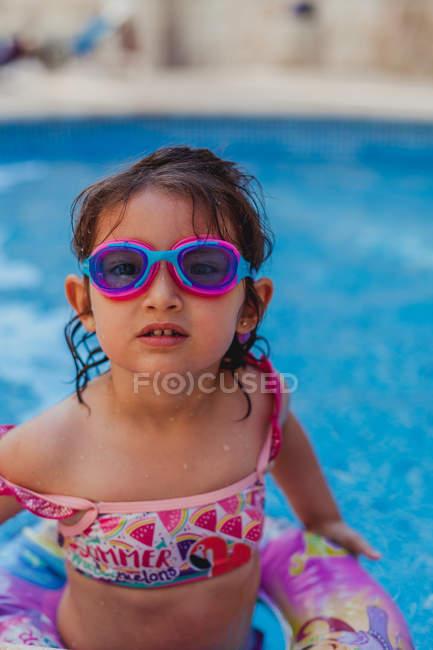 Criança em óculos de natação tomando banho na piscina com água azul clara e olhando para a câmera — Fotografia de Stock