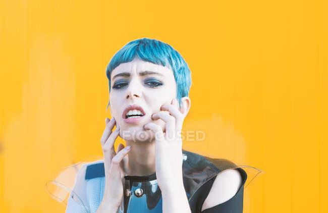 Sensual mujer joven en vestido futurista de moda en el pavimento contra la pared de color amarillo brillante - foto de stock