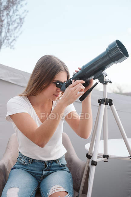 Young attractive woman sitting on chair and looking through telescope at sky — Stock Photo