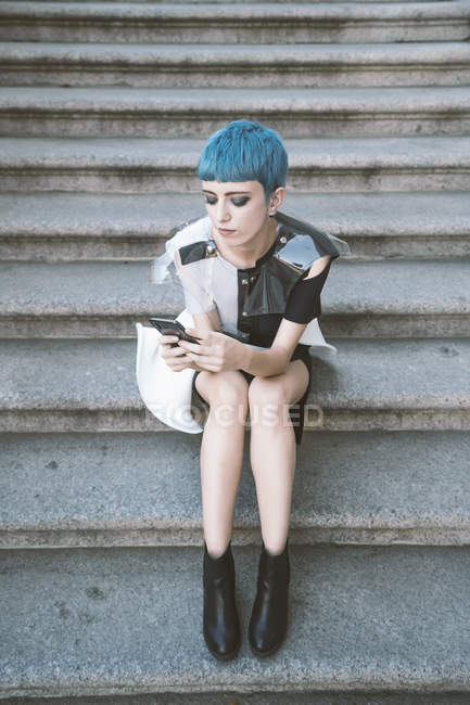 From above of young woman with short blue hair and in trendy futuristic dress listening to music with phone on street steps — Stock Photo