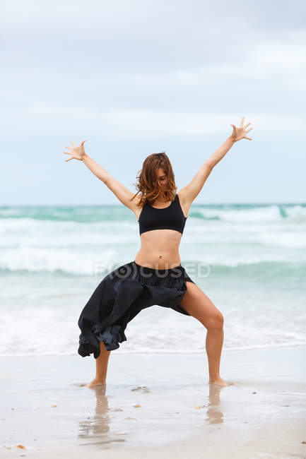 Attractive woman in black outfit dancing on sand near waving sea — Stock Photo