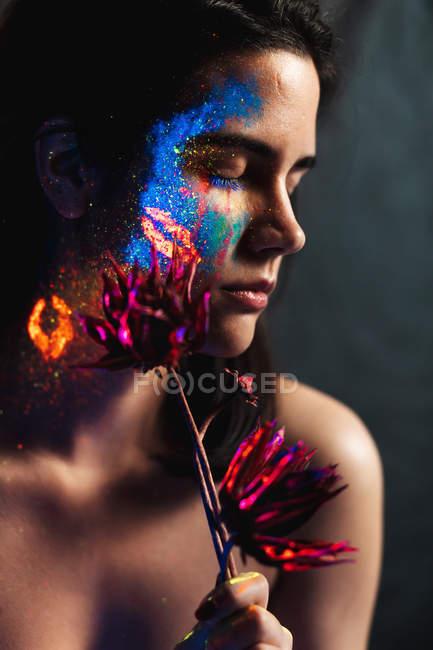 Retrato de una hermosa joven con los ojos cerrados cubiertos de pintura luminosa en la cara sosteniendo una flor - foto de stock