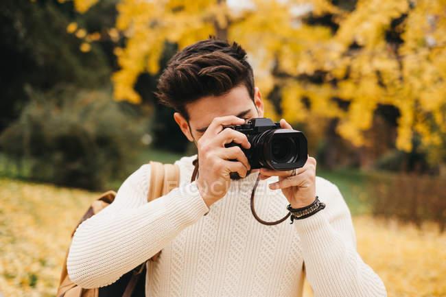 Bonito jovem fotógrafo de pé no parque de outono e tirar foto com câmera — Fotografia de Stock