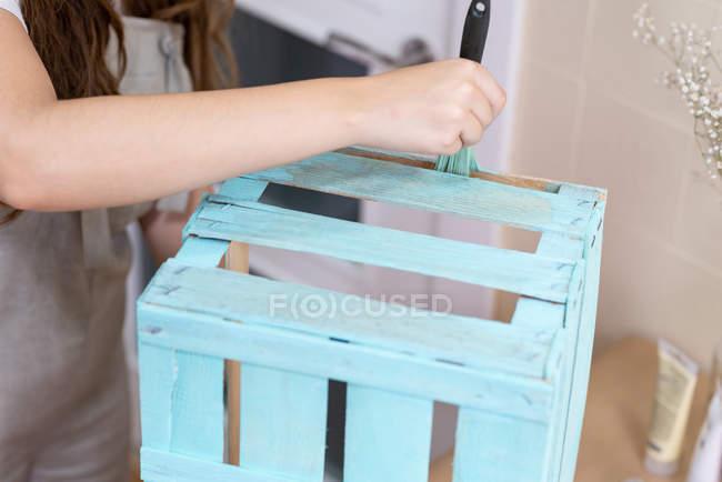 Крупним планом жіночої ручного фарбування дерев'яна коробка в блакитному кольорі з пензлем — стокове фото