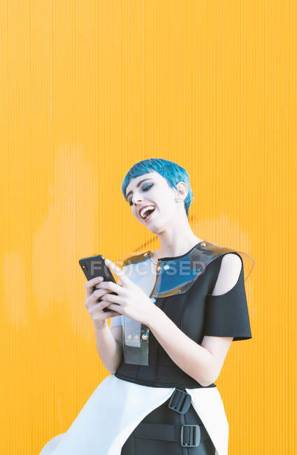 Young woman in futuristic dress laughing and texting on smartphone while standing against bright yellow wall — Stock Photo