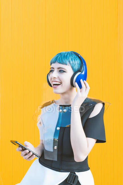 Mulher informal alegre em fones de ouvido e smartphone ouvindo música enquanto está de pé contra a parede amarela vívida — Fotografia de Stock