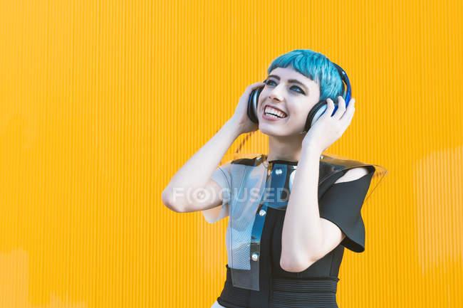 Allegro giovane donna in abito alternativo alla moda sorridente e ascoltare musica in cuffia contro il muro giallo — Foto stock