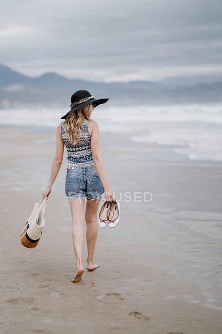 Rückansicht einer Frau mit schwarzem Hut, die eine Strandtasche in der Hand hält und den malerischen Blick auf das Meer genießt — Stockfoto